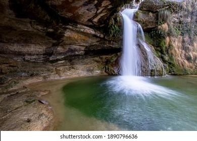 Bonita cascada al lado de una cueva