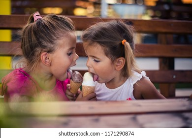 It's nice when it's shared. Two little girl eating ice cream together in park. Close up. Space for copy.