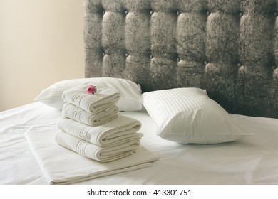 Nice white bed sheets with brown bed in hotel room