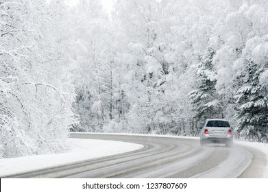 Nice winter scene with snowy trees, road and car. Driving home for Christmas. Slippery road.