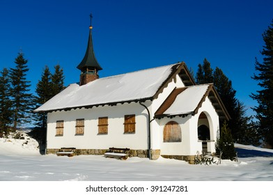 A nice wintery scene in the alps with a rural church located on top of a hill. The building is constructed in the typical european style.