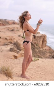 Nice woman in bikini standing on a seaside cliff with chain bound hands and praying