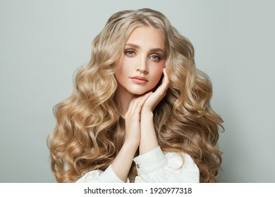 Nice woman fashion model with clear skin and healthy wavy hair on white background