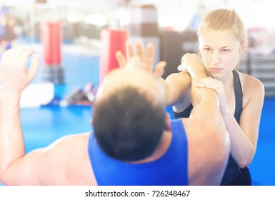 Nice woman is fighting with trainer on the self-defense course for woman in sport club