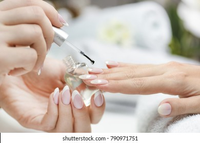 Nice woman hands applying lacquer polish. Nail care salon. Manicure nails paint with beautiful lacquer.