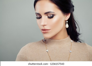 Nice woman in jewelry gold earrings with diamond and pearls