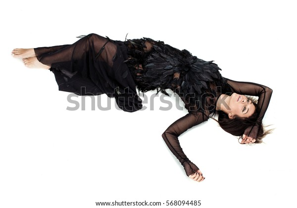 Nice woman laying in studio on the floor and raising her hands with long black sleeves up and thinking. She is wearing nice long dark diaphanous dress with a lot of feathers