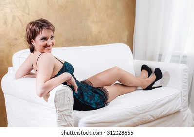 Nice woman in luxury lingerie resting on white sofa