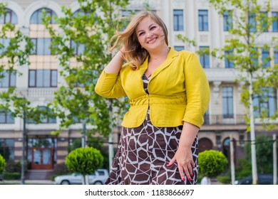 Nice woman of plus size, American or European appearance walks in the city enjoying life. A young lady with excess weight, stylishly dressed at the center of the city. Natural beauty