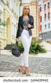 Nice woman posing on the street against the background of the building, wearing a jacket, pants and corset