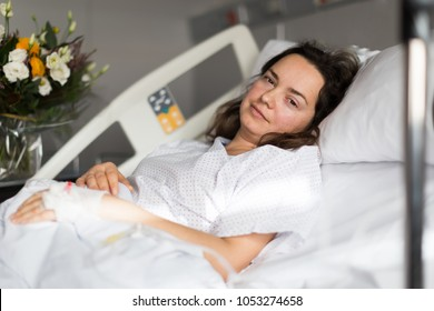 Nice woman is satisfied of visit her and lying on the bed in hospital indoor