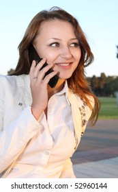 Nice woman talking on mobile phone at nature background