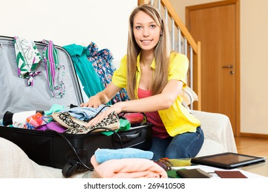 Nice woman trying packs big suitcase