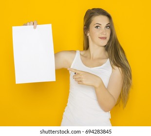 Nice young attractive woman holding blank paper and point on it. Mockup template for your design with copy space on orange background