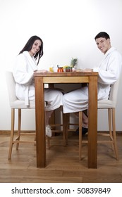 Nice young couple in the morning eating their breakfast in their home, wearing white towel robe.