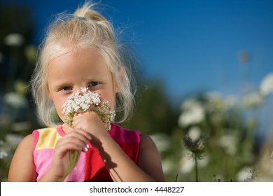 A nice young girl sniffing on yarrow
