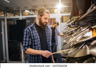 Nice young hipster stand at cymbals and touches them with drum stick. He looks at them. Another young man stand behund and touch cymbals as well.