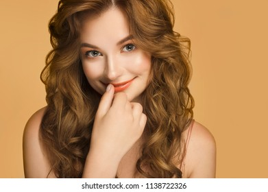 Nice young smiling woman with long red wavy silky hair, natural make up looking shy embarassed at camera with hand near lips isolated on yellow background. People emotions and feelings. Beauty concept