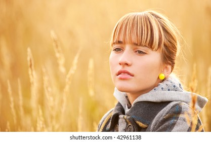 Nice young woman against yellow ripe field of wheat.