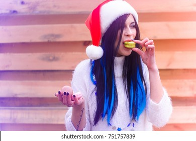 Nice young woman in the New Year's cap actively eats sweets and cookies. Rationing sweet in the New Year and Christmas holidays, girls and diet. Harm of sugar on the human body, joy in everyday life