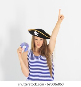 Nice young woman with pirate cd or dvd disk and hat with skull and crossbones. Concept of software piracy and copyrighting