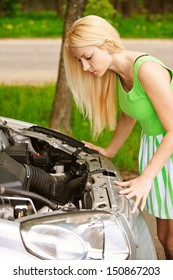 Nice young woman repairing car, against green of summer park.