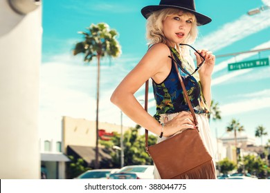 Nice young woman walking in the street wearing hat, sunglasses. Fashion summer photo. Bright colors