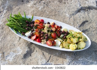 A nicely arranged Salad Nicoise on a large stone