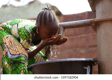 Nicely Braided African Girl Washing Her Face With Fresh Water At the Borehole
