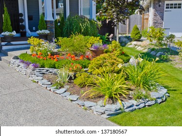 Nicely decorated flower bed, some flowers and nicely trimmed bushes on the front yard. Landscape design.
