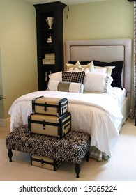 A nicely decorated guest bedroom with a collection of suitcases, a ceiling fan and a padded headboard