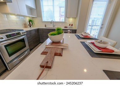 Nicely decorated kitchen counter, table with bowl with some green salad on the cutting deck and the kitchen at the back. Interior design.