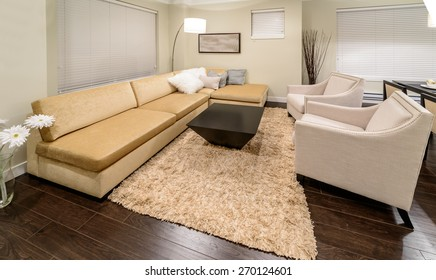 Nicely decorated modern living room with sofa and chairs and a coffee table. Interior design of a new house.