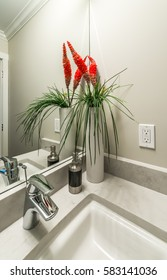 Nicely decorated modern washroom, bathroom with and some flowers in the vase at the sink. Interior design.