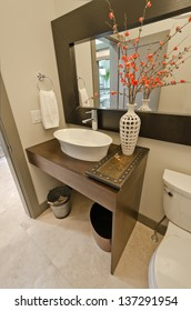 Nicely decorated modern washroom with the toilet, vase with some flowers and decorative buckets.  Interior design.