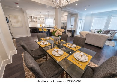 Nicely decorated and served dining, lunch  room table with family room and the kitchen at the back. Interior design.