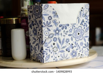 Nicely designed box of napkins on the kitchen table. Square box of tissues with blue floral design/illustration.