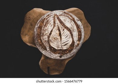 A nicely round freshly baked organic wheat-spelt bread, scored with an ornament in shape of a leaf. Bread is on a piece of rustic wood.