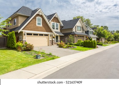Nicely trimmed and manicured garden in front of a luxury house on a sunny summer day. Street of houses in the suburbs of Canada.