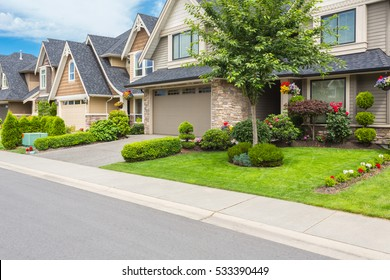 Nicely trimmed and manicured garden in front of a luxury house. Street of homes in the suburbs of Canada.