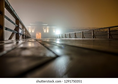 Nicholas gate and wooden bridge of Daugavpils Fortress in fog at night