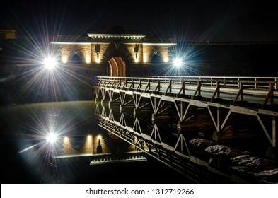 Nicholas Gate and wooden bridge of Daugavpils Fortress reflecting in the water of moat at night.