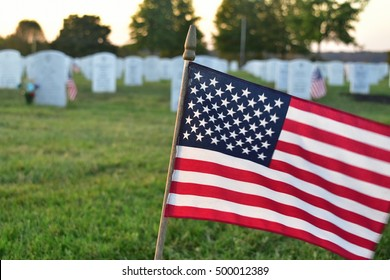 Nicholasville, Kentucky, U.S.A.  Camp Nelson National Cemetery. October 17, 2016.  Small American flag waving in foreground with white marble tombstones in the background.  Editorial Use Only.