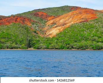 Nickel and iron ore rich soil of New Caledonia, red hills and lush green tropical vegetation.