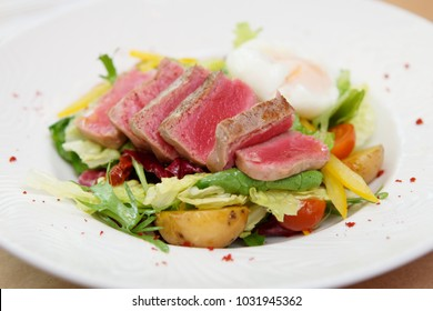 Nicoise salad of rare fried tuna, potato, salad mix and poached egg in white plate