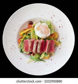Nicoise salad of rare fried tuna, potato, salad mix and poached egg in white plate, isolated on black