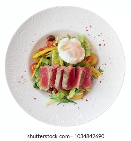 Nicoise salad of rare fried tuna, potato, salad mix and poached egg in white plate, isolated on white
