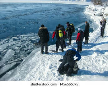 Nicola village on Lake Baikal, Russia - March 10, 2012: divers in professional diving equipment preparing to dive under the ice of Lake Baikal. Outdoor winter diving.