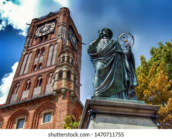 Nicolaus Copernicus monument in Torun in Poland. inscribed Nicolaus Copernicus Thorunensis. Photo taken from ground level. The old town hall tower with large clock in the background. Sunny, blue sky.