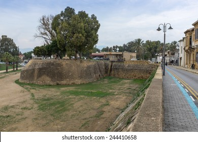 NICOSIA, CYPRUS - DECEMBER 17, 2014 : Ancient Venetian Walls and the Zahra Bastion next to a row of Ottoman townhouses in the historic Arabahmet quarter of Turkish north Nicosia in North Cyprus.